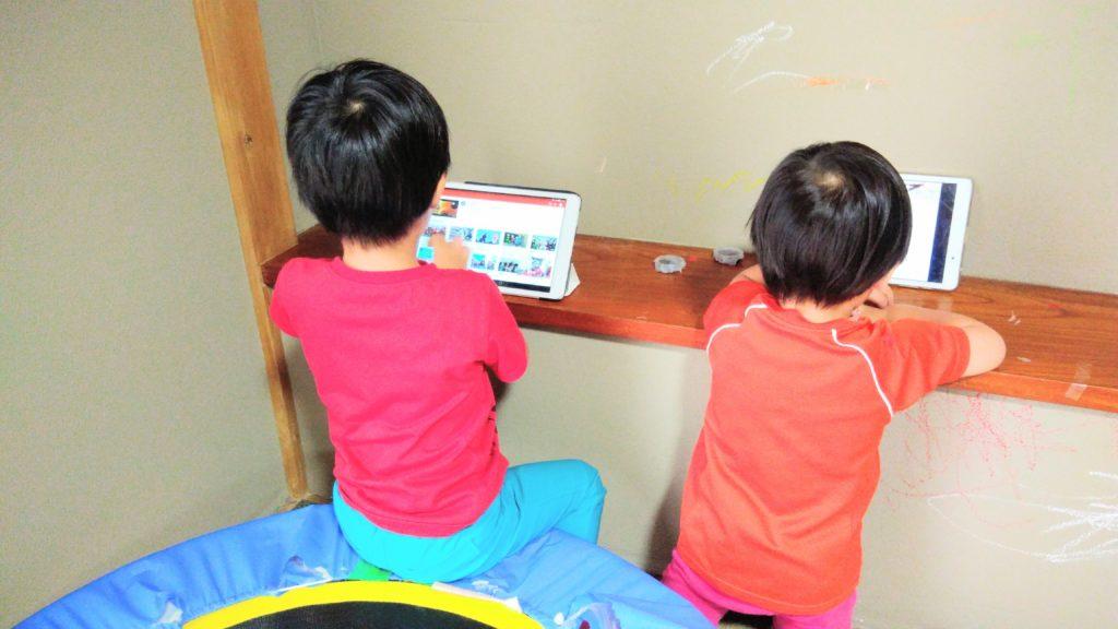 タブレットを見る子ども2人
