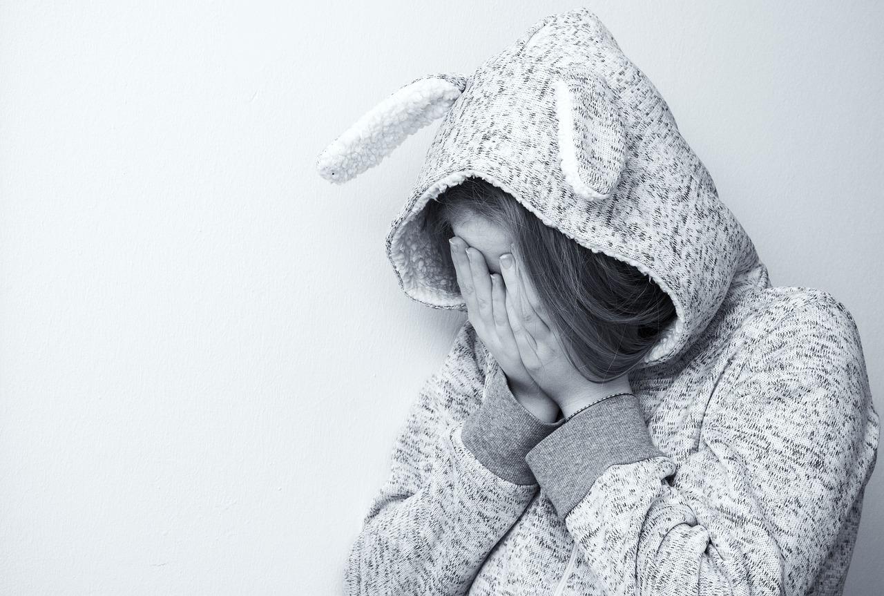 両手で顔をおおって悲しむ女性