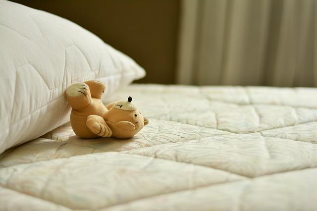 ベッドに寝転ぶクマのぬいぐるみ