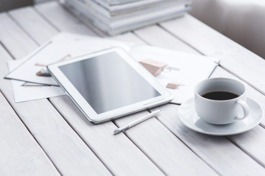 机の上にコーヒーとタブレット