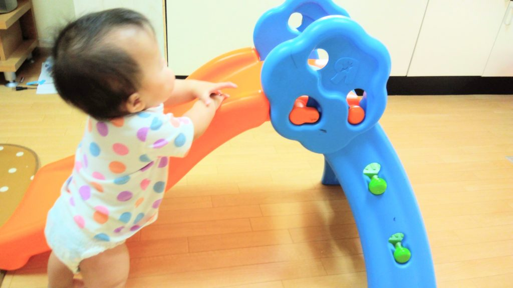 すべり台につかまる赤ちゃん