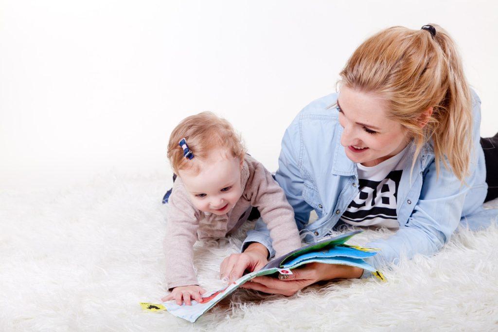 ママと子どもが寝転んで本を読んでいる