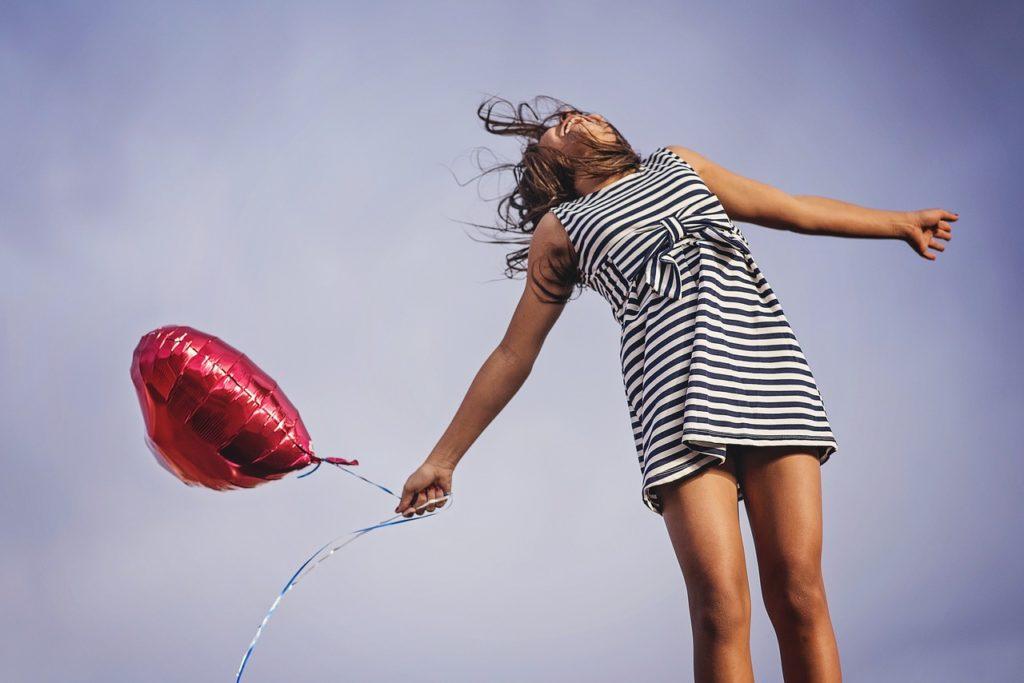 空をあおぐ風船をもった女性