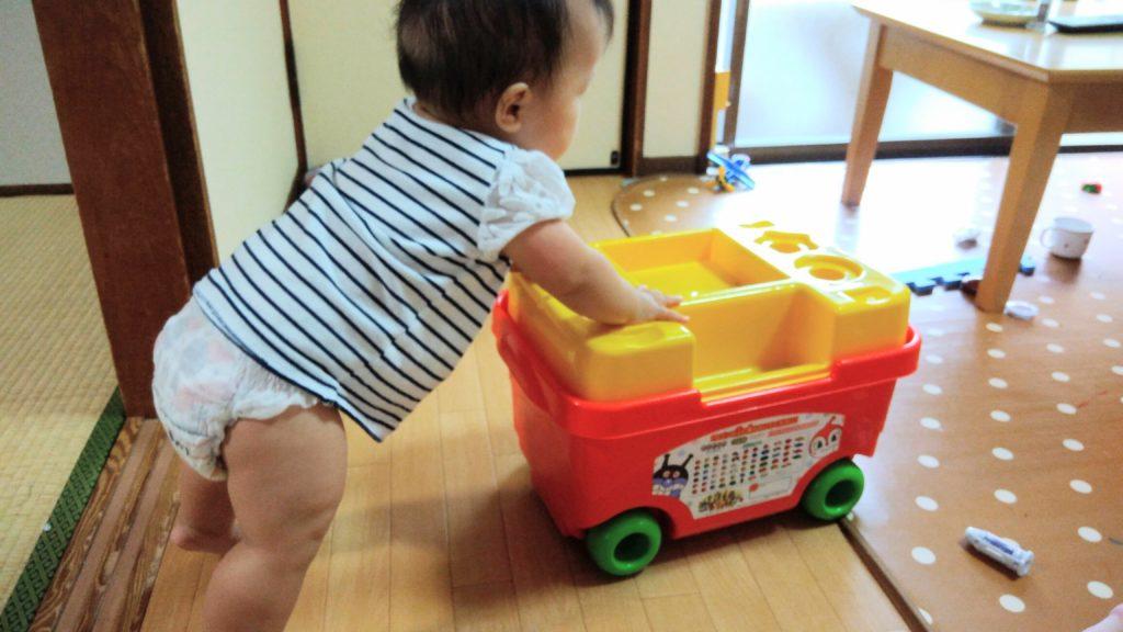 おもちゃ箱を押して歩く赤ちゃん